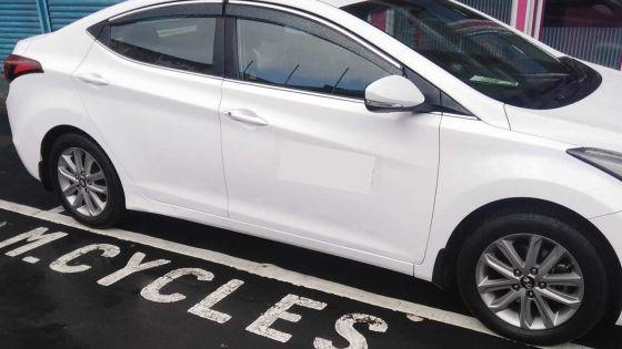 Une voiture stationnée sur un parking réservé aux deux-roues