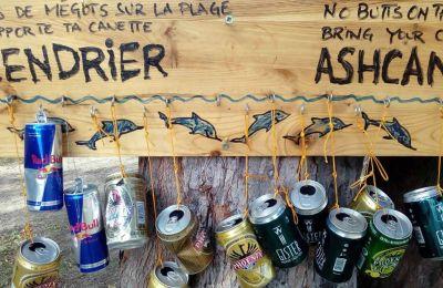 Des cannettes de boissons alcoolisées et énergétiques ont été suspendues à un panneau en bois, cloué à un filao, sur lequel il est écrit : « Pas de mégots sur la plage, rapporte ta canette ».